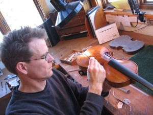 Folland working on a violin